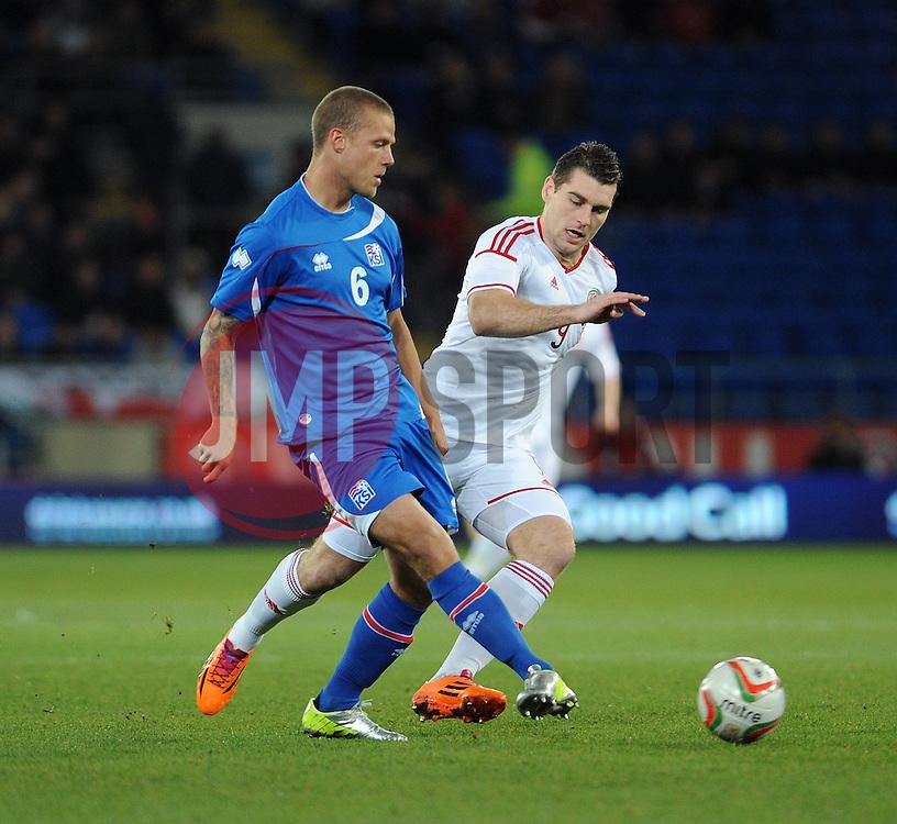 Sam Vokes of Wales (Burnley) chases down Ragnar Sigurdsson (FK Kransnodar) of Iceland - Photo mandatory by-line: Dougie Allward/JMP - Tel: Mobile: 07966 386802 03/03/2014 -