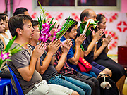 "24 JUNE 2017 - BANG KRUAI, NONTHABURI: People pray before a ""resurrection"" or rebirthing ceremony at Wat Ta Kien (also spelled Wat Tahkian), a Buddhist temple in the suburbs of Bangkok. People go to the temple to participate in a ""Resurrection Ceremony."" Thai Buddhists believe that connecting people by strings around their heads, which are connected to a web of strings suspended from the ceiling, amplifies the power of the prayer. Groups of people meet and pray with the temple's Buddhist monks. Then they lie in coffins, the monks pull a pink sheet over them, symbolizing their ritualistic death. The sheet is then pulled back, and people sit up in the coffin, symbolizing their ritualist rebirth. The ceremony is supposed to expunge bad karma and bad luck from a person's life and also get people used to the idea of the inevitability of death. Most times, one person lays in one coffin, but there is family sized coffin that can accommodate up to six people. The temple has been doing the resurrection ceremonies for about nine years.     PHOTO BY JACK KURTZ"