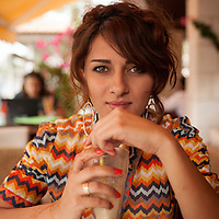 Young Palestinian professional Manal Abdallah drinks a fruit shake at an upscale cafe in Ramallah, the West Bank.