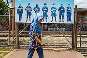 27 OCTOBER 2012 - SUNGAI KOLOK, NARATHIWAT, THAILAND:   A Muslim woman walks past a sign at the train station in Sungai Kolok, province of Narathiwat, Thailand. encouraging Thai students to cooperate with and support state security services. Sungai Kolok has been a center of extremist violence. Several car bombs have been detonated in the city, which is on the Malaysian border and very popular with Malaysian tourists. More than 5,000 people have been killed and over 9,000 hurt in more than 11,000 incidents, or about 3.5 a day, in Thailand's three southernmost provinces and four districts of Songkhla since the insurgent violence erupted in January 2004, according to Deep South Watch, an independent research organization that monitors violence in Thailand's deep south region that borders Malaysia.   PHOTO BY JACK KURTZ