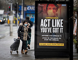 © Licensed to London News Pictures. 02/02/2021. London, UK. A woman wearing a face mask walks past an NHS coronavirus poster on a bus stop in West Ealing, West London, where a new South African variant of coronavirus has ben discovered. Door-to-door delivery of free home test kits is to start in the area in an attempt to slow the spread of the more aggressive strain of the virus. Photo credit: Ben Cawthra/LNP