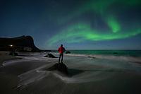 Person stands on tidal rock to watch northern lights - aurora borealis above Myrland beach, Flakstadøy, Lofoten Islands, Norway