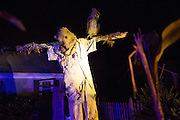 """A scarecrow and owl loom over Chris Baker's haunted yard in South Yarmouth, MA. Every year Baker sets up an elaborate Halloween display in his yard and on Halloween, neighborohood residents walk through his frightening """"vortex"""" of horror while trick or treating."""