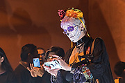 A foreign tourist wearing skeleton face paint takes a camera phone photo of an ofrenda altar during the Dead of the Dead festival in San Miguel de Allende, Mexico. The multi-day festival is to remember friends and family members who have died using calaveras, aztec marigolds, alfeniques, papel picado and the favorite foods and beverages of the departed.