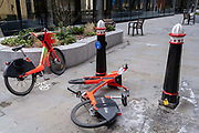 Two Uber rental bikes have been discarded by their rider, left in the middle of a deserted pedestrian street during the third lockdown of the Coronavirus  pandemic, in the City of London, the capitals financial district, on 10th February 2021, in London, England.