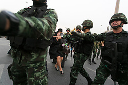 © Licensed to London News Pictures. 26/05/2014. A PDRC supporter is escorted out by Army for her own safety after taunting anti-coup protestors during a Anti-Coup protest in Bangkok Thailand. Today Thailand's King formally approved Thai army chief General Prayut Chan-O-Cha as head of the nation's new military junta.  Photo credit : Asanka Brendon Ratnayake/LNP
