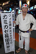 "Man dressed in martial arts gear advertising a Japanese magazine for console game players. The bandana says ""Kamikaze""."