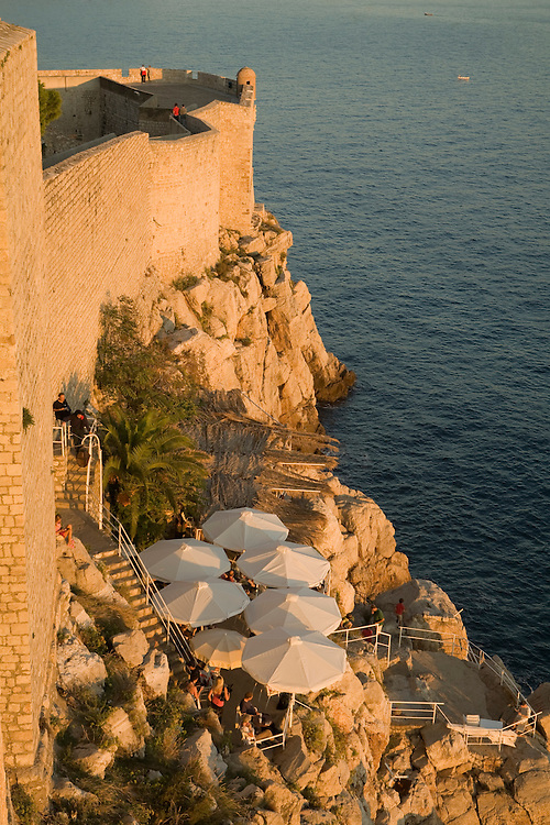 Europe, Croatia, Dalmatia, Dubrovnik.  Old city walls (built 10th century) above outdoor cafe and the Adriatic Sea. The historic center of Dubrovnik is a UNESCO World Heritage site.