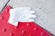 Brooklyn, NY - 23 March 2020. Discarded surgical gloves are a familiar sight in the streets and on the sidewalks.