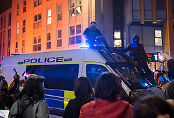"""© Licensed to London News Pictures;21/03/2021; Bristol, UK. Two protestors sit on the roof of a police van as it tries to reverse past another police van which has been set on fire as police clash with protesters outside New Bridewell Police Station on Sunday evening during a """"Kill the Bill"""" protest against Police, Crime, Sentencing and Courts Bill takes place through the centre of Bristol during the Covid-19 coronavirus pandemic in England. The Bill proposes new restrictions on protests. Lockdown restrictions have been partly lifted to allow people to gather outdoors socially in households, bubbles, or to meet one person from another household, but the police say protests are not allowed under the current Covid regulations. Photo credit: Simon Chapman/LNP."""