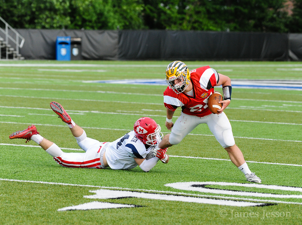 North Squad's Daniel Monagle, from Masconomet Regional High School, tries to pull down South Squad's Shane Frommer, from King Phillip Regional High School, during the Shriner's All-Star Football Classic at Bentley University in Waltham, June 22, 2018.   [Wicked Local Photo/James Jesson]