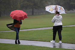 © Licensed to London News Pictures. 27/09/2021. London, UK. Members of the public shelter under umbrellas as they walk in Greenwich Park during a rain shower .Rain showers are forecasted to continue in parts of London and South East England for the rest of the week.  Photo credit: George Cracknell Wright/LNP
