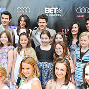 The neighborhood kids couldn't wait to have their picture taken with the Jonas Brothers.
