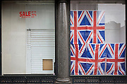 British Union jack flags-themed tourist window, now closed with displays removed after recent sale.