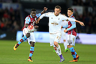 Idrissa Gana Gueye of Aston Villa (l) gets the ball ahead of Gylfi Sigurdsson of Swansea city. Barclays Premier league match, Swansea city v Aston Villa at the Liberty Stadium in Swansea, South Wales on Saturday 19th March 2016.<br /> pic by  Andrew Orchard, Andrew Orchard sports photography.