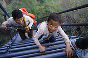 LIANGSHAN, CHINA - NOVEMBER 19: <br /> <br /> Children climb the steel ladder on the cliff on November 19, 2016 in Liangshan Yi Autonomous Prefecture, Sichuan Province of China. A new steel ladder opened in early November to replace the old vines on the cliff up to the Atuler village in Liangshan. Over 20 students, from the school at the foot of the 1,400-meter-tall mountain, could climb the steel ladder as a safer and shorter way leading home on the 800-meter cliff at Meigu River Canyon. <br /> ©Exclusivepix Media