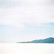 Passenger Bus on Salar de Uyuni salt flats, Potosi, Bolivia. The Salar de Uyuni are the worlds largest salt flats.