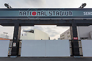 An entrance gate to National Stadium partly obscures the demolition of the stadium inside., Shinjuku, Tokyo, Japan. Friday March 6th 2015. Large scale demolition work officially began, March 5th to remove  the old stadium, which was the venue for the 1964 Olympics, after many delays. Construction of the new Olympic stadium for the 2020 games is scheduled to begin in October 2015