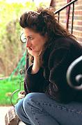 Thoughtful woman age 32 sitting on front steps.  St Paul Minnesota USA