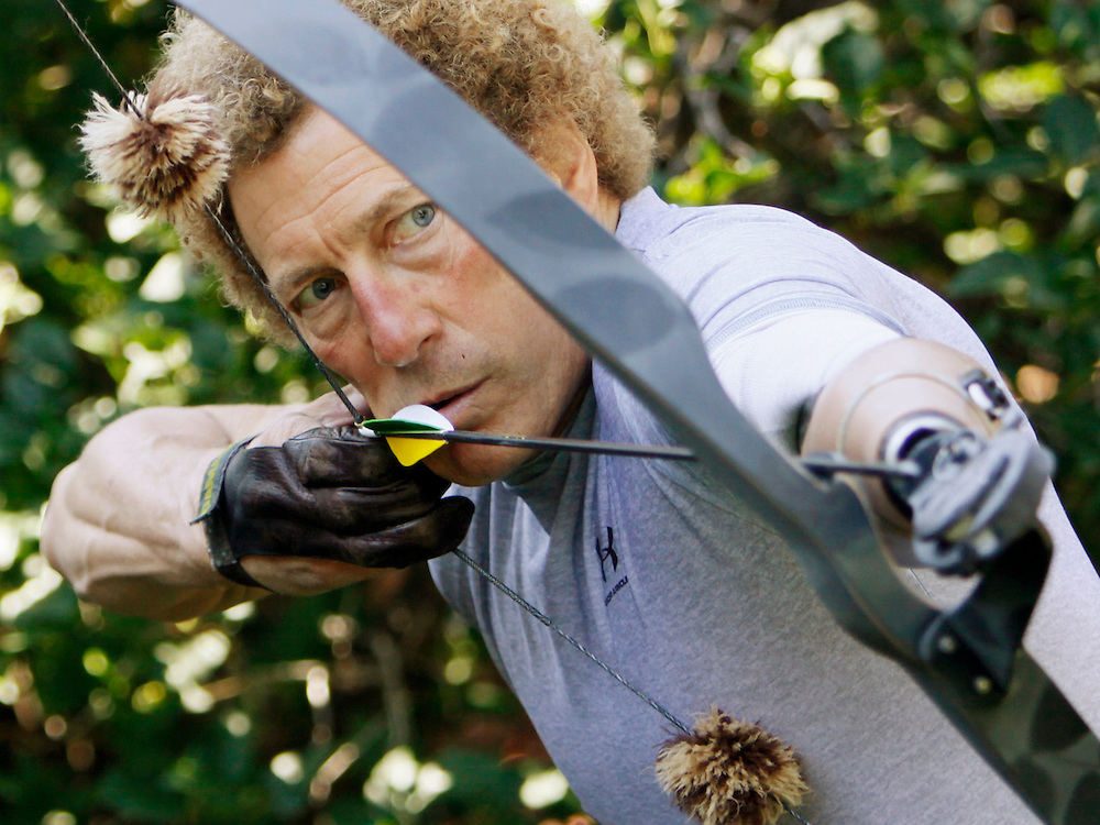 Bob Radocy of TRS Inc. shoots his bow with a grip prehensor hand replacement at his home in Boulder, Colorado August 20, 2009. Radocy designs and builds prosthetic attachments that allow amputee athletes to participate in multiple sports.  REUTERS/Rick Wilking (UNITED STATES)