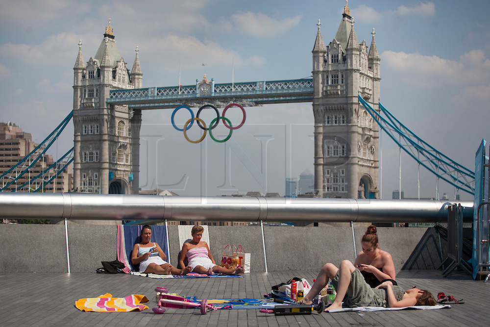 © licensed to London News Pictures. London, UK 25/07/2012. People sunbathing outside the City Hall on 25/07/12 in London. Photo credit: Tolga Akmen/LNP
