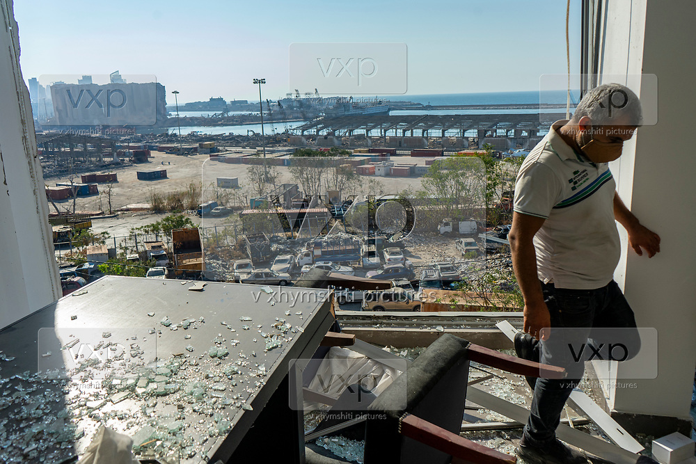 A man looks through a broken window of a residential building towards the grain silo in the Port of Beirut on Saturday, Aug 22, 2020, nearly 3 weeks after the explosion that devastated the city. (VXP Photo/ Matt Kynaston)