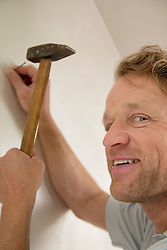 Portrait smiling man working hammer nail wall