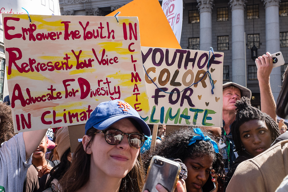 """20 September 2019 - New York, NY.  Thousands of students as well as adults gathered in New York for the Global Climate Strike, meeting in Foley Square near the Federal Government buildings and New York's City Hall, and marching downtown to Battery Park, where Swedish climate activist and spokesperson Greta Thunberg addressed the crowd. Two signs read """"Empower the youth / represent your voice / advocate for diversity / in climate,"""" and """"Youth of color for climate."""""""