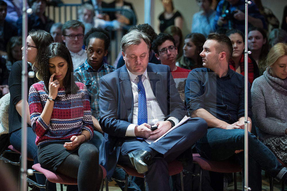 © Licensed to London News Pictures . 27/02/2015 . Leeds , UK . ED BALLS using his mobile phone as Ed Miliband speaks at the launch of the Labour Party's fourth election pledge at a speech on young people . British Labour Party leader Ed Miliband and Shadow Chancellor Ed Balls at Leeds College of Music today ( Friday 27th February 2015 ) . Photo credit : Joel Goodman/LNP