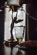 The Absinth Ritual at Hemingway Bar in Prague. A spoon with a sugar cube is placed above the quality Absinth and the sugar is slowly getting liquid throug the drops of water coming out of the Art Noveau water tank above.