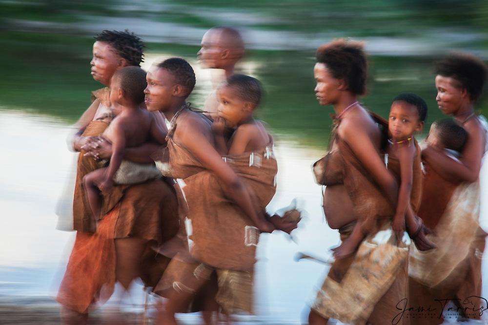 A motion-blur of  San bushmen women and children walking, Kalahari, Botswana, Africa