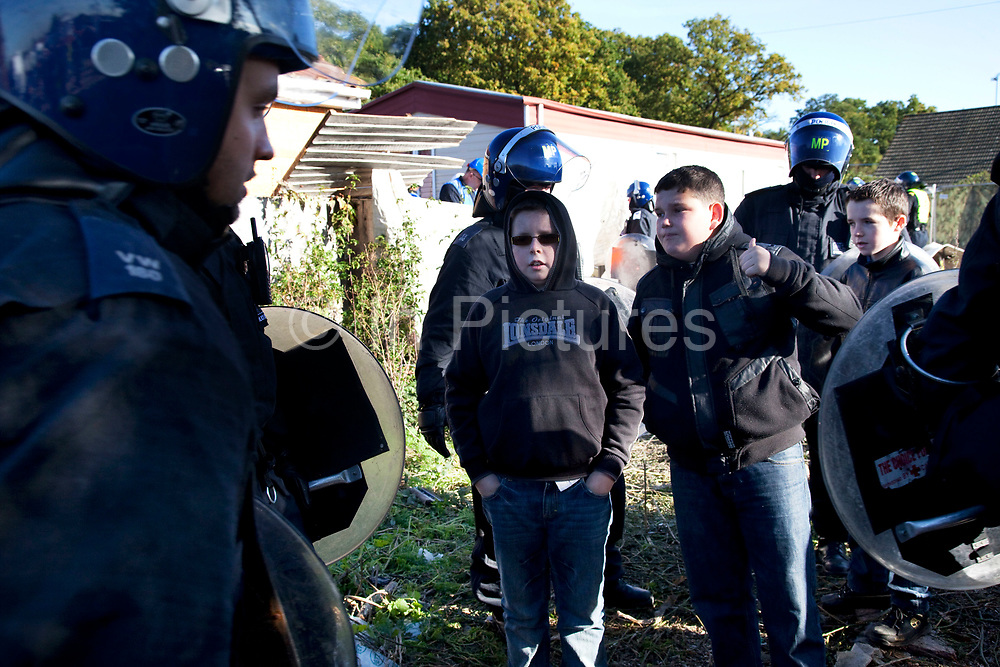 Young traveller children chat to police. Travellers at Dale Farm site prior to eviction. Riot police and bailiffs were present on 20th October 2011, as the site was cleared of the last protesters chained to barricades. Dale Farm is part of a Romany Gypsy and Irish Traveller site in Crays Hill, Essex, UK<br /> <br /> Dale Farm housed over 1,000 people, the largest Traveller concentration in the UK. The whole of the site is owned by residents and is located within the Green Belt. It is in two parts: in one, residents constructed buildings with planning permission to do so; in the other, residents were refused planning permission due to the green belt policy, and built on the site anyway.