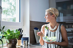Young woman eating salad in the kitchen and smiling, Bavaria, Germany