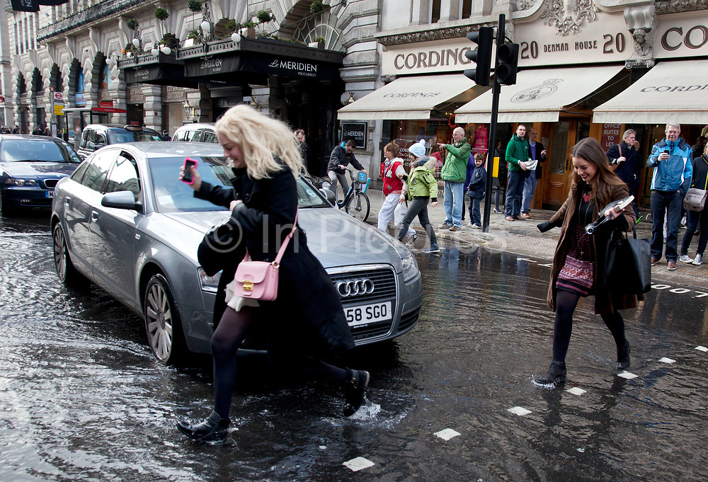 London, UK. Saturday 2nd March 2013. Burst water main causes flooding disruption in central London. Cars and other vehicles pass through the deep water gathering on Piccadilly.