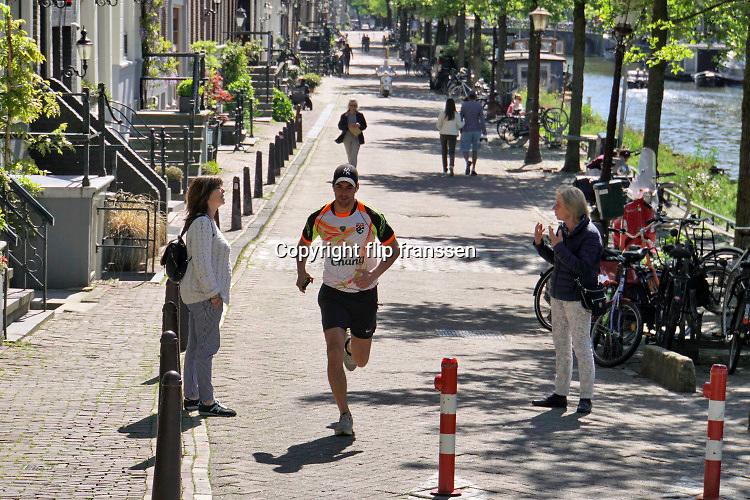Nederland, Amsterdam, 7-5-2020 Een man, sporter, hardloper, jogger, loopt tussen twee mensen door die afstand tot elkaar houden in het centrum van de stad . Hierdoor wordt de afstand tussen de drie te klein. Per 1 juni is het dragen van mondbescherming verplicht in het ov, openbaar vervoer, sport . Foto: Flip Franssen