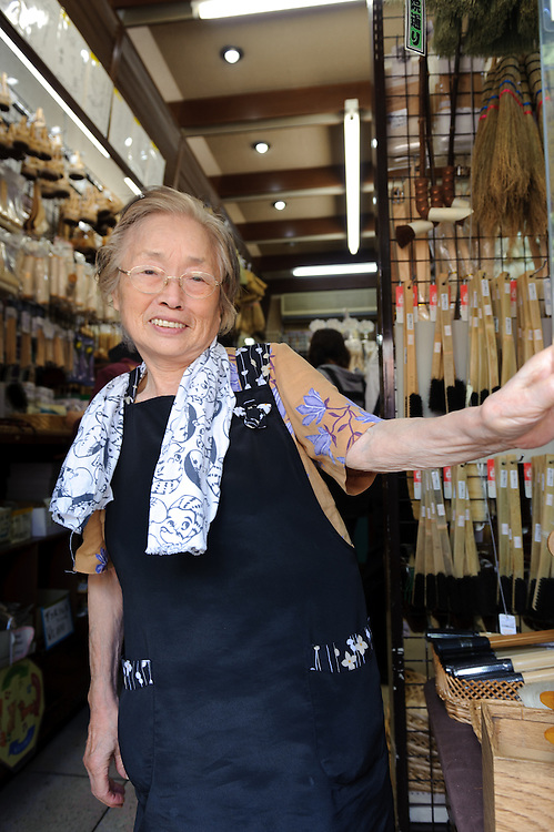 An elderly lady serving customers in Kanaya brush shop, Asakusa, Tokyo, Japan, August 28, 2011. Sensoji is one of the oldest temples in Tokyo, and the shopping arcades around it have sold visitors souvenirs for centuries.