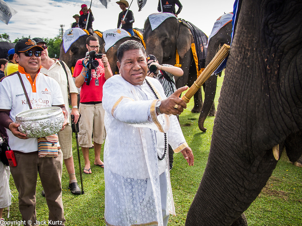 "29 AUGUST 2013 - HUA HIN, PRACHUAP KHIRI KHAN, THAILAND: A Brahmin priest blesses the elephants before the King's Cup Elephant Polo Tournament in Hua Hin. The tournament's primary sponsor in Anantara Resorts and the tournament is hosted by Anantara Hua Hin. This is the 12th year for the King's Cup Elephant Polo Tournament. The sport of elephant polo started in Nepal in 1982. Proceeds from the King's Cup tournament goes to help rehabilitate elephants rescued from abuse. Each team has three players and three elephants. Matches take place on a pitch (field) 80 meters by 48 meters using standard polo balls. The game is divided into two 7 minute ""chukkas"" or halves. There are 16 teams in this year's tournament, including one team of transgendered ""ladyboys.""    PHOTO BY JACK KURTZ"