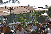 A cafe in Bordeaux city, outside seating terrasse with sun shades parasol, people drinking and eating
