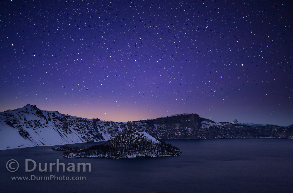 Crater Lake with Wizard Island under a starry sky. Crater Lake is a caldera lake in the western United States, located in south-central Oregon. It is the main feature of Crater Lake National Park and is famous for its deep blue color and water clarity. The lake partly fills a nearly 2,148-foot deep caldera that was formed around 7,700 years ago by the collapse of the volcano Mount Mazama. Two separate exposures were combined for this image.