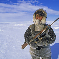 BAFFIN ISLAND, Nunavut, Canada. Inuit hunter Jayko Apak (MR) looks for seals on frozen Sam Ford Fjord, Baffin Bay.