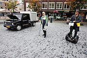 Een bezoeker van het Uitfeest probeert op de Neude in Utrecht een Segway uit, op de achtergrond staat een elektrisch aangedreven auto. Met het Uitfeest is in Utrecht het cultureel seizoen weer geopend. Traditioneel valt het samen met de autoloze zondag, waarbij dit jaar opvallend veel aandacht is voor de elektrische voertuigen.<br /> <br /> A man is trying to ride a segway during the start of the cultural season in Utrecht. At the same day the city of Utrecht is free of cars.