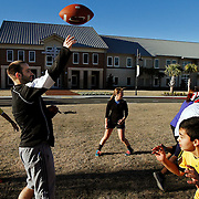 """Matt Dakolios, Dean of Students at John Paul II Catholic School, center left, tosses the ball to a teammate during a game of two-hand touch football with students during the winter workout club outside of John Paul II Catholic School on January 6, 2015.  """"The winter workout club provides exercise for kids who aren't winter sport athletes,"""" said Dakolios."""