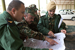 © Licensed to London News Pictures. 30/03/2015. Erbil, Iraq. Peshmerga officers plan movements on a map during a training exercise at a military training area near Erbil, Iraq.<br /> <br /> The training is part of a four week long package, the first to be held with a complete peshmerga battalion, run by coalition forces mobile training teams (MTT) in Kurdistan with the aim to make the peshmerga more efficient in combatting the Islamic State. Photo credit: Matt Cetti-Roberts/LNP