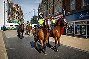Police officers on horse back patrol the streets of Dover to keep apart members of Kent Anti Racism Network and far right facist groups who were also gathering to blockade the port of Dover on the 5th September 2020, Dover, Kent.  Members of Kent Anti Racism Network gathered today in Dover, Kent to stand in solidarity with those fleeing war, poverty and persecution making the extremely dangerous crossing to seek sanctuary in the UK.  (photo by Andrew Aitchison / In Pictures via Getty Images)