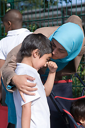 Mother comforting son at school gates