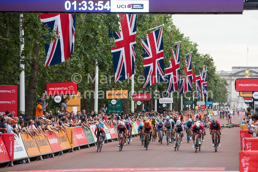 London, UK. 3 August, 2019. Elite riders from sixteen of the world's top professional female cycling teams approach the finish on the Mall during the Prudential RideLondon Classique. The Classique, which is the richest one-day women's race in the world, covers 20 laps of a tight circuit of 3.4 kilometres around St James's Park and Constitution Hill. Defending champion Kirsten Wild, who crossed the finishing line first, was disqualified following the collision visible behind.