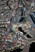 Nederland, Amsterdam, Stationplein, 12-05-2009; Stationseiland met rechts het Centraal Station en onder in beeld de Sint Nikolaaskerk. Voor het station het Open Havenfront met de bouwput van de Noord/Zuidlijn, In deze bouwput wordt boormachine opgebouwd, de tunnelboormachie zal als eerste onder het water van het Damrak gaan boren (bij de gele bouwkraan). Overview of the construction of the underground (metro) in  the Central Station area in Amsterdam from the air. .Swart collectie, luchtfoto (toeslag); Swart Collection, aerial photo (additional fee required).foto Siebe Swart / photo Siebe Swart