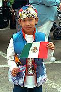 Spectator age 8 holding Mexican flag at Cinco de Mayo.  St Paul Minnesota USA