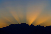 Crepuscular sun rays emenate from behind Mount Constance in the Olympic Mountain Range as seen from the Puget Sound, Washington, USA.