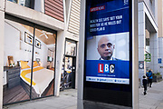On the day that the UK has recorded 50,000 Covid cases, the first time in three months, Conservative MP and government Health Secretary, Sajid Javid appears on a news screen in the East End, with the latest headline about his refusal to ask the public to wear face coverings, or to further enforce England's Plan B to control surging Covid cases despite appeals from leading doctors, and instead, for the public to simply have booster jabs, on 21st October 2021, in London, England.